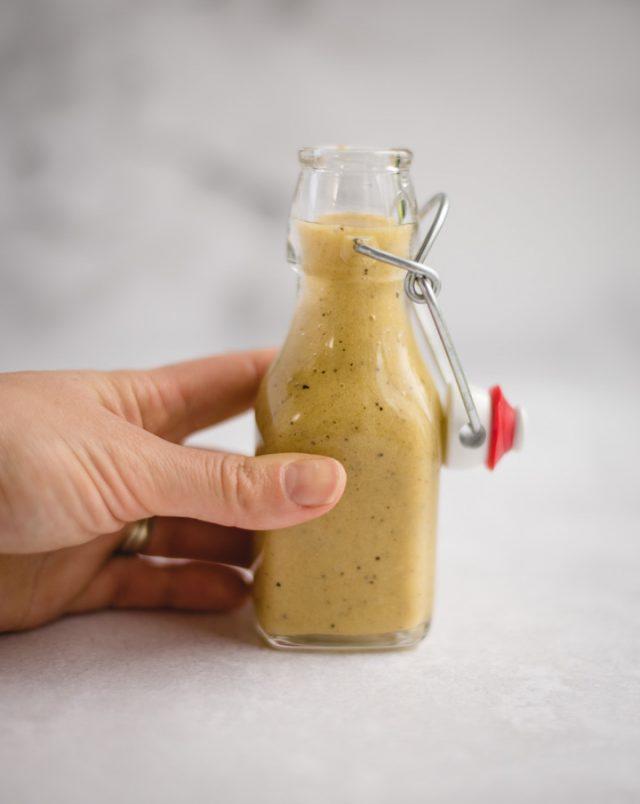 hand holding jar of lemon vinaigrette