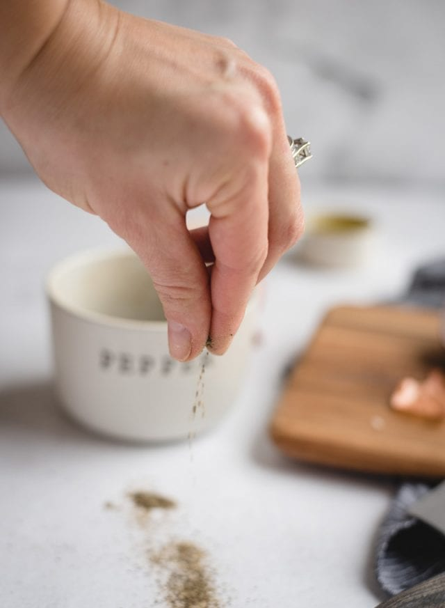 hand sprinkling black pepper with white background