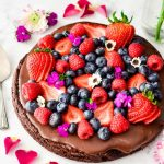 chocolate pizza topped with berries on white background