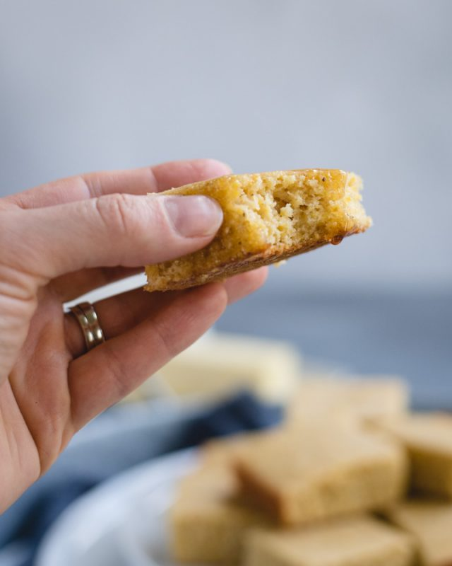 up close picture of a hand holding a piece of cornbread with a bite taken out and honey dripping off