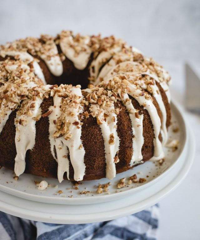 banana bundt cake with cream cheese frosting and nuts sprinkled on top