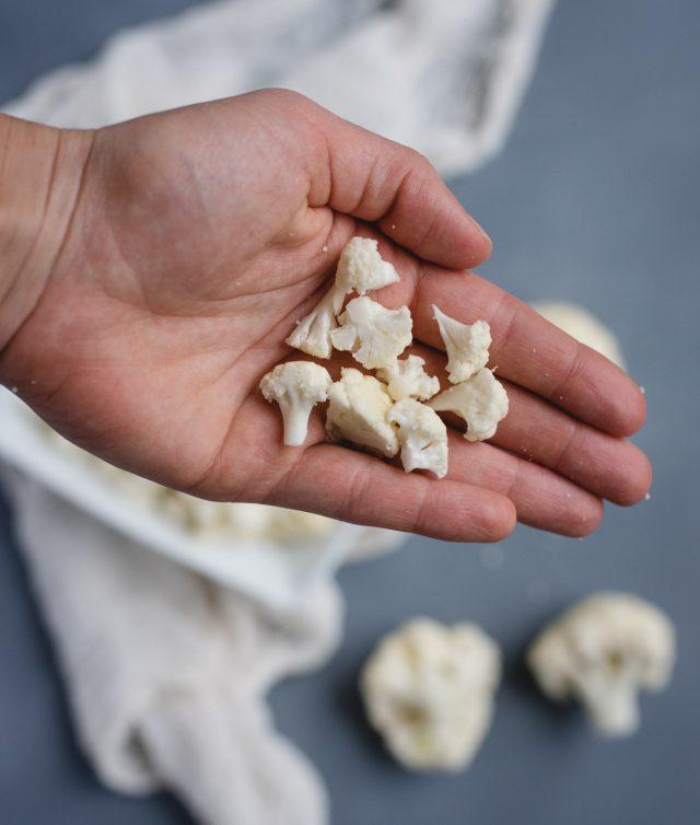 hand holding chopped up cauliflower florets