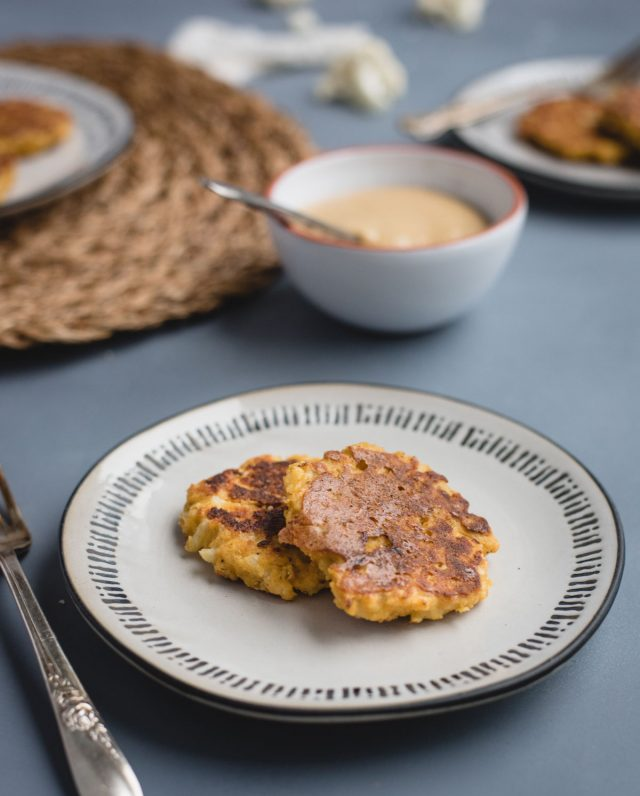 white plate with two cauliflower fritters on a blue background