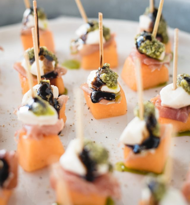 close up picture of a tray of melon, mozzarella, prosciutto skewers topped with pesto and balsamic glaze