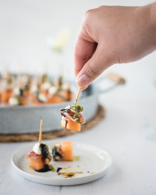 hand grabbing toothpick prosciutto melon skewer off a plate with more in background
