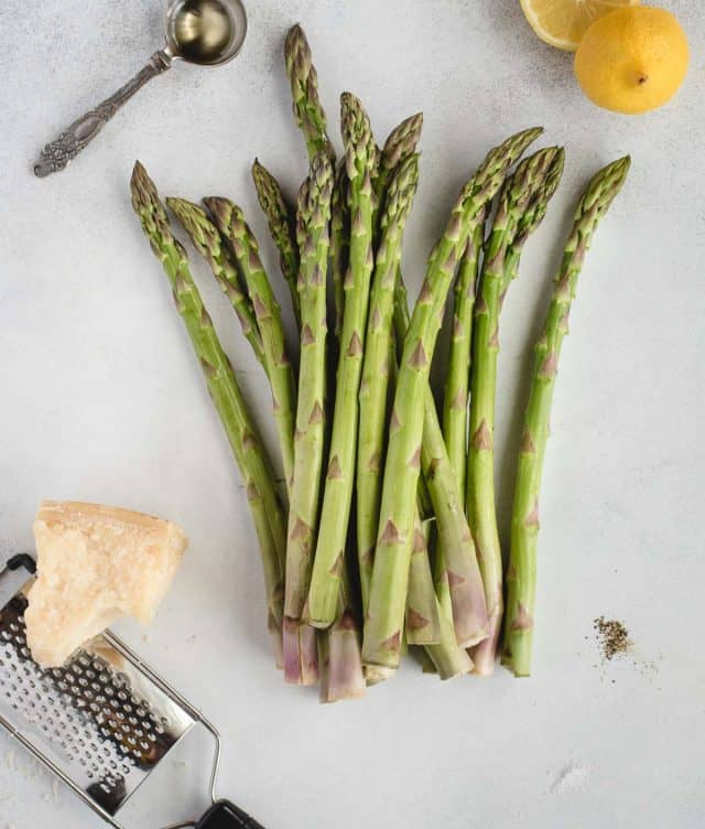 ingredients for air fryer asparagus laid out on a gray background