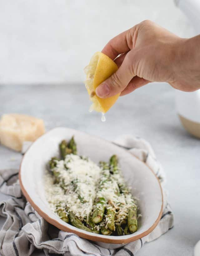 hand squeezing lemon over a plate of asparagus