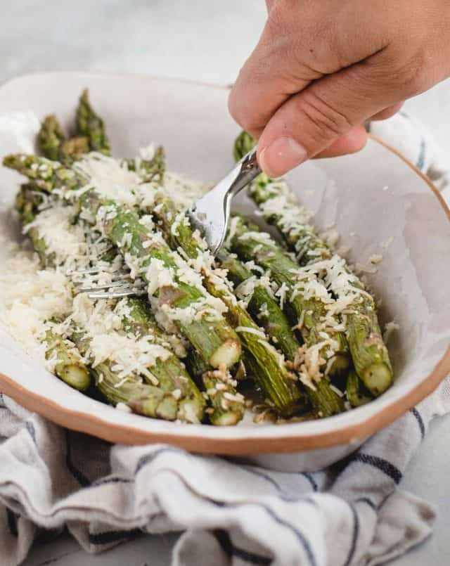 hand scooping parmesan covered asparagus spears off of a white plate