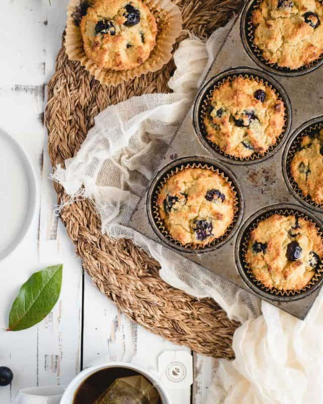 Close up overhead picture of blueberry muffins in a tin on a white background
