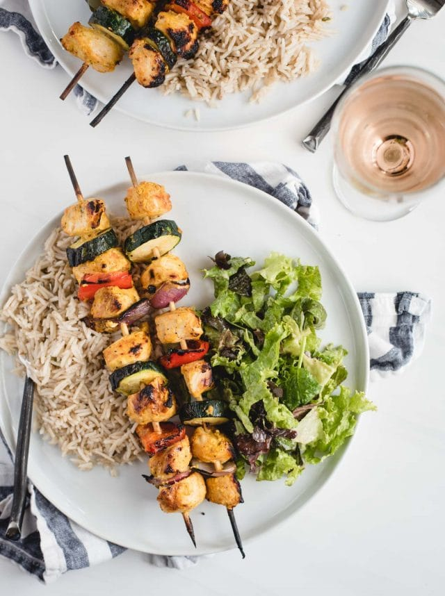 close up overhead picture of two plates of marinated chicken kabobs, salad, and rice with white wine on a white table