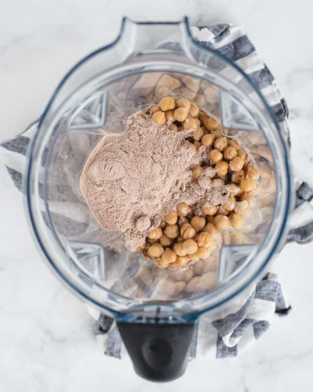 blender with chocolate protein powder and chickpeas in it
