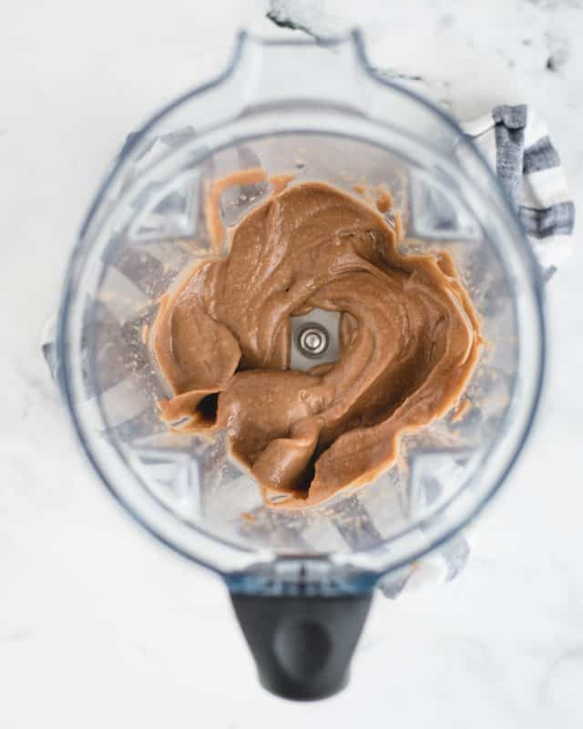 blender with blended up chocolate hummus in it